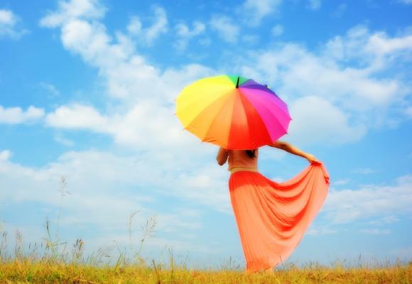Mujer en campo con paraguas de colores