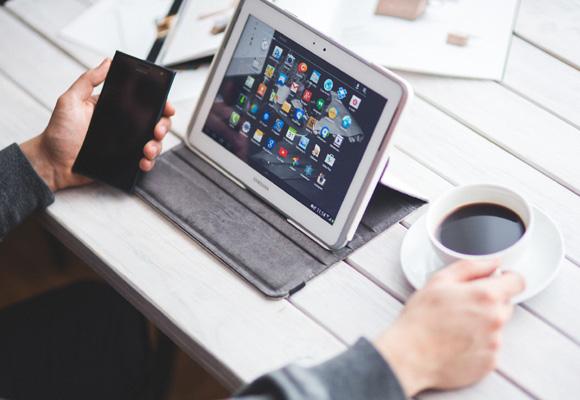 Hombre tomando café con tableta y smartphone