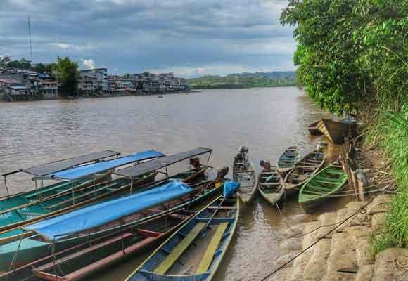 la ciudad de Santa María de Nieva desde la orilla de enfrente, y barcas típicas para el desplazamiento de los aguajun